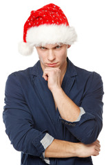 Upset male wearing Santa hat, isolated on white
