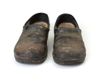 Front view of old dirty clogs on a white background