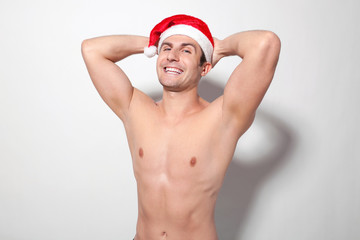 Shirtless man wearing Santa hat laughing