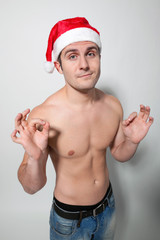 Muscular shirtless man wearing Santa hat showing OK