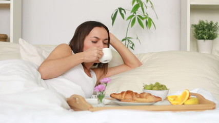Attractive happy woman eating breakfast in bed