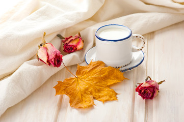 Breakfast with milk. Vintage cup, dry roses and maple leaf