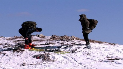 Skiers preparing for skiing on top of mountain