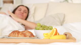 Woman waking up in bed with breakfast, dolly shot