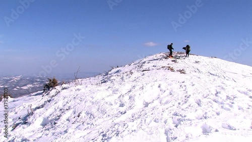 Skiers preparing on top of mountain for skiing