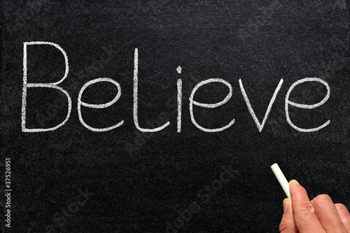 Believe, written with chalk on a blackboard.