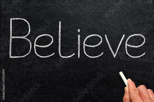 Believe, written with chalk on a blackboard.