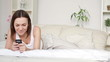 Happy woman in bed sending sms, text message, dolly shot