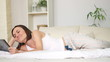 Happy woman with digital tablet lying in bed, dolly shot