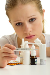 Young woman having flu with thermometer and pills