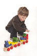 cute little boy playing with colorful wooden train