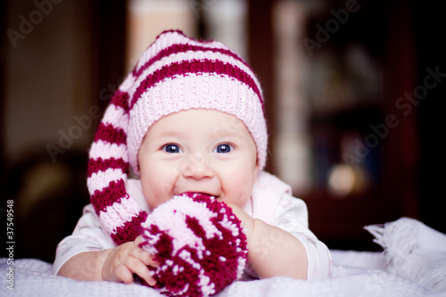 baby girl in striped purple hat with pompom in her hands