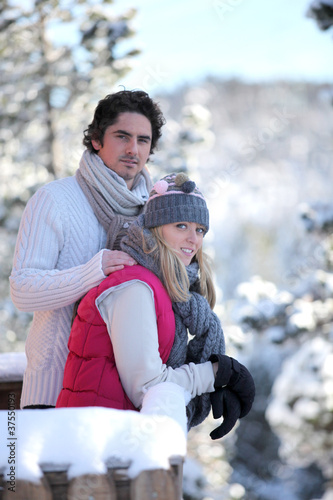 Young couple leaning out of their ski cabin