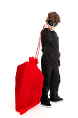 Child stealing Santa's sack isolated on white
