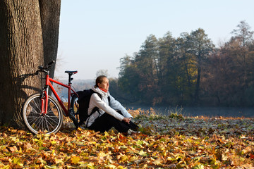 Peppy woman cyclist enjoy the recreation autumn morning in natur