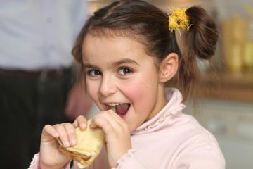 Happy girl eating a pancake