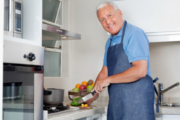 Man Cutting Vegetables At Kitchen Counter
