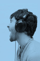 Profile of a man with ear-phones. Blue tone.