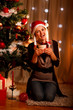 Happy young woman near Christmas tree hugging present