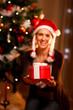 Smiling woman near Christmas tree presenting gift box