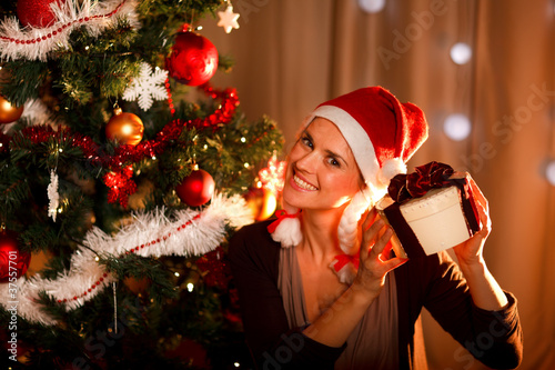 Interested woman near Christmas tree shaking present box