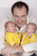 happy father with his  identical baby twin daughters