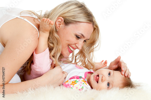 Loving mother plaing with her baby;  child is lying on sheepskin