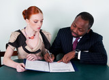 Black man and redhead young woman sitting with documentation