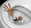 Businessman sinking in toilet bowl