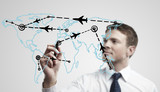 Fototapety Young business man drawing an airplane routes on world map