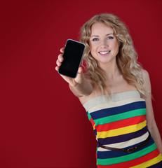 Beautiful woman holding mobilephone towards camera