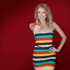 Beautiful blond woman showing thumb up on red background