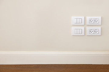 Power outlet and  light switch on the wall