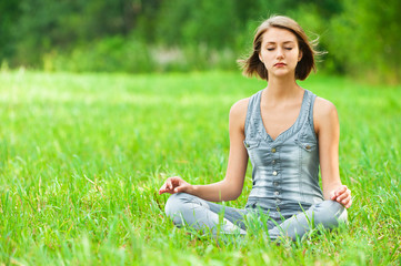 woman meditating sitting on grass