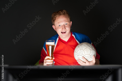 Young man holding soccer ball and beer and watching tv translati