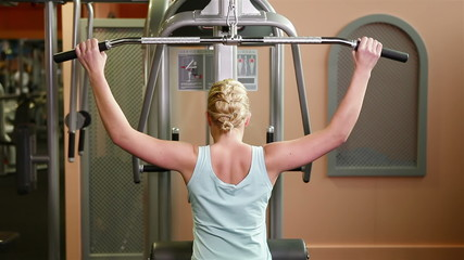 Woman using lat machine in gym