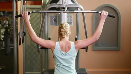 Woman using lat machine in gym