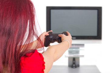 Frau spielt Videogame vor Fernseher