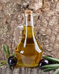 Olivenölflasche vor Kork mit schwarzen Oliven und Blättern