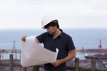 Ingenieur mit Zeichnung in der Hand vorm Hafen