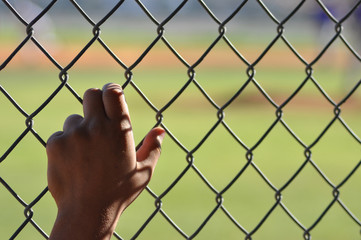 Lonely hand on chain link fence at a baseball field