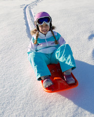 Happy winter - little girl  sledging downhill
