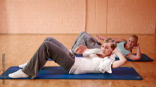 Women doing crunches in gym