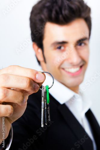 Portrait of attractive young man showing some keys