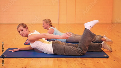 Women stretching their legs in fitness center