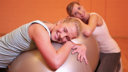 Women relaxing after workout on gym ball