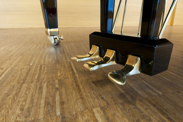 golden piano pedals of a concert grand piano on concert stage
