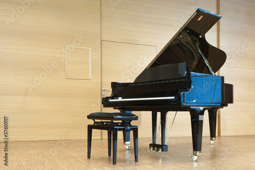 opened black grand piano with stool on a wooden concert stage - 37600117