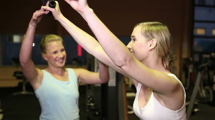 Fitness trainer helping woman in gym