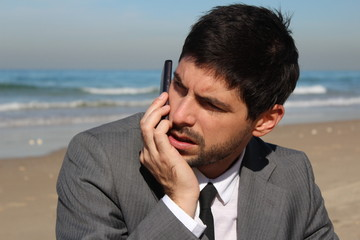 A businessman is speaking on the mobile phone at the beach